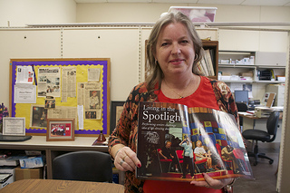 Seasoned Performers artistic director Ellise Mayor, 56, shows off some past press coverage in the theater troupe's Birmingham headquarters. Photo by Jordyn Taylor.